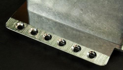A 6 csavaros tremoló és sustain block, jól látható az él kiképzése a furatoknál